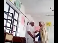 A 70 yrs old man sex not far from 30 yrs bold lady in classroom.